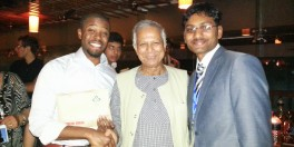 Living Proof Founder Mujahid Washington receives event gift from Grameen Bank Founder, Nobel Laureate, Presidential Medal of Freedom and Congressional Gold Medal recipient Mohammed Yunus, with Living Proof India Entrepreneur, Rupesh Manne at Social Business Day 2013.